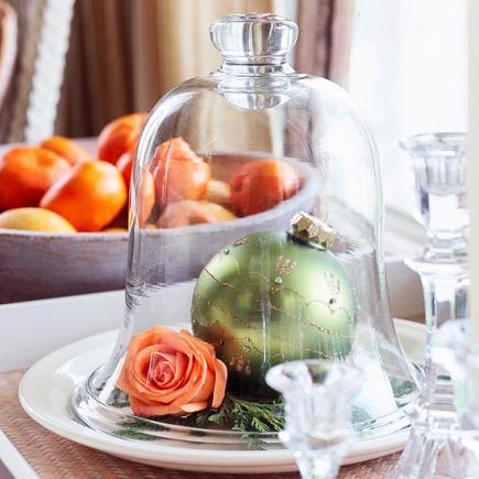 Centro de mesa con una rosa y y una bola en una campana