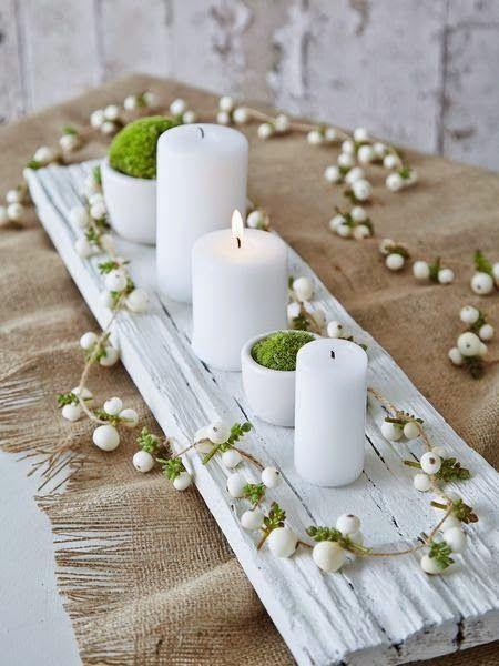 Bandeja con velas blancas y elementos verdes