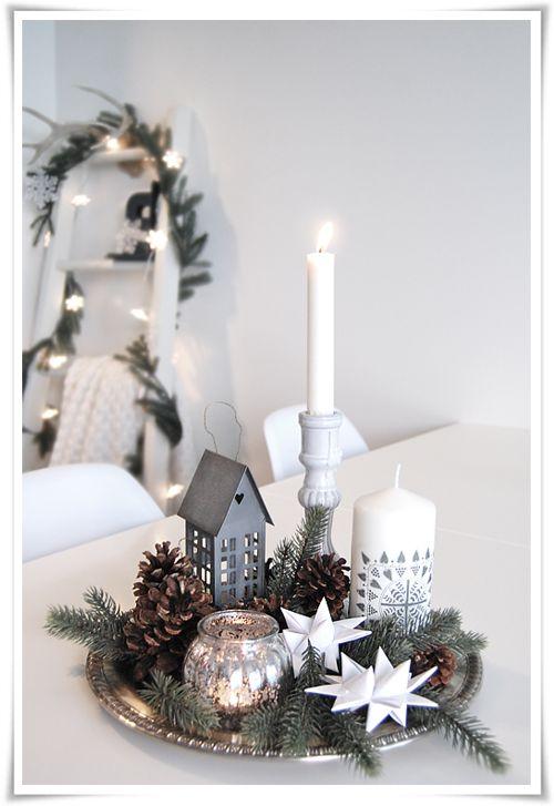Velas blancas y edificios de navidad para decorar mesa