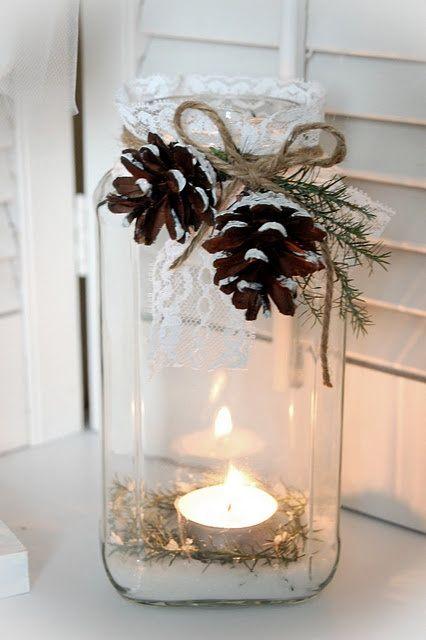 2 piñas decorando mesa de navidad con vela
