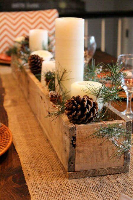 Vela blanca en cajón de madera y piñas